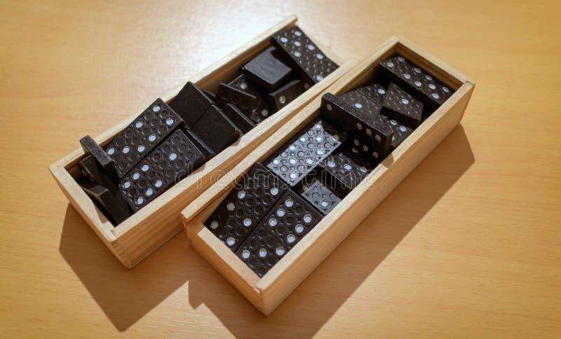 Assortimento delle mattonelle di legno di domino in scatole immagine stock