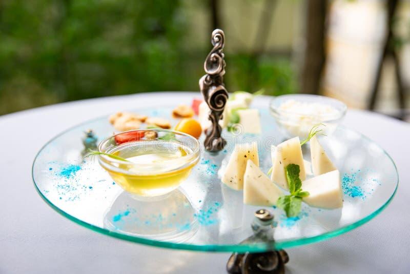 Assortimento di formaggio Composizione delle varietà differenti di formaggio con miele, dadi sulla tavola di vetro fotografie stock libere da diritti