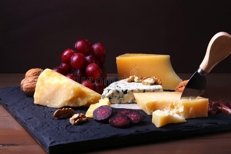 Assortimento di formaggio con i frutti, l'uva, i dadi ed il coltello del formaggio su un vassoio di legno del servizio immagini stock
