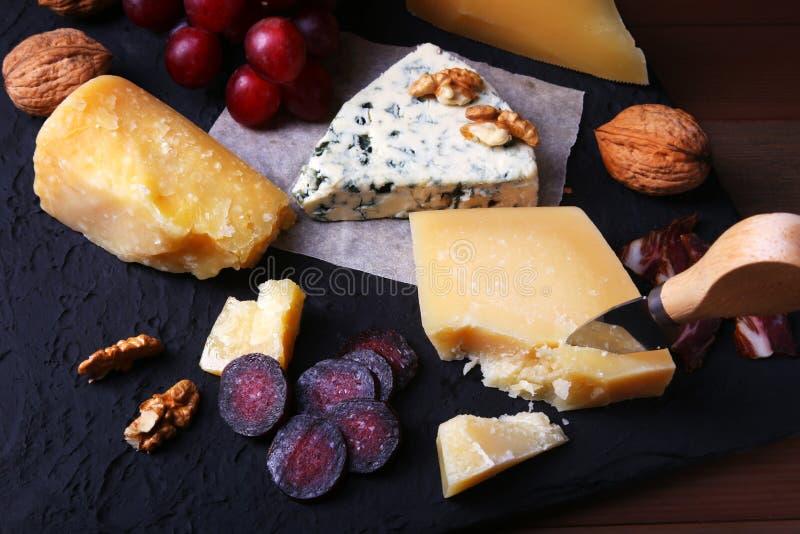 Assortimento di formaggio con i frutti, l'uva, i dadi ed il coltello del formaggio su un vassoio di legno del servizio immagine stock