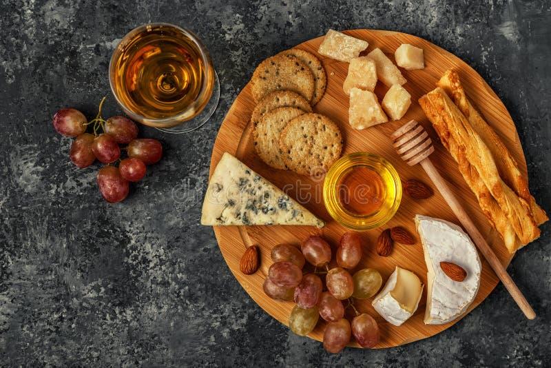 Assortimento di formaggio con vino, miele, i dadi e l'uva fotografia stock libera da diritti