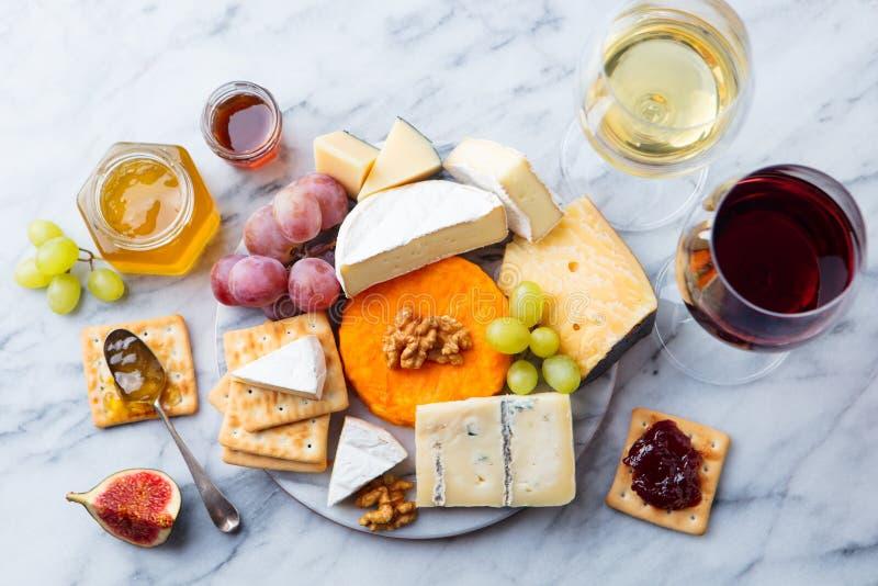Assortimento di formaggio, uva con vino rosso e bianco in vetri Fondo di marmo Vista superiore immagine stock libera da diritti