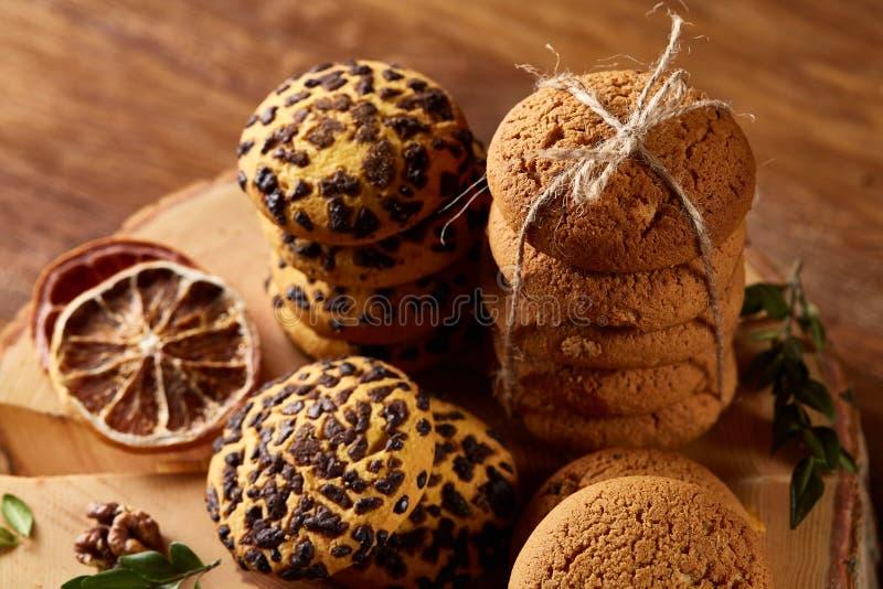 Assortimento dolce dei biscotti su un ceppo di legno rotondo sopra fondo di legno rustico, primo piano, fuoco selettivo fotografia stock