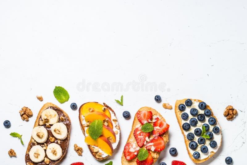 Assortimento dolce del pane tostato con frutta fresca e le bacche su bianco fotografie stock libere da diritti