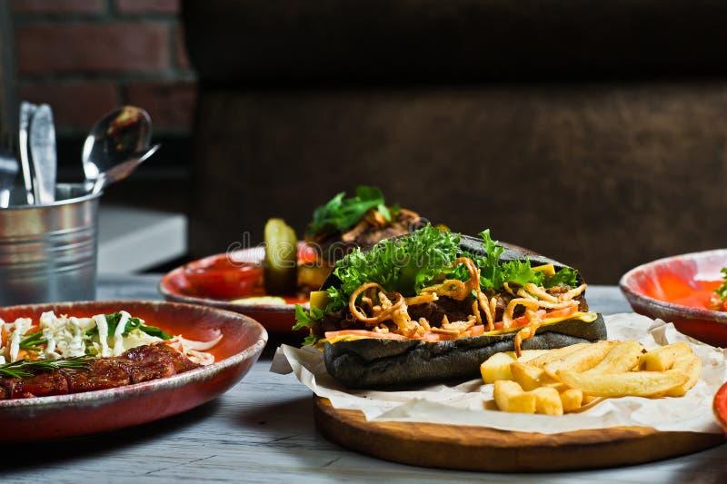 Assortimento gastronomico delle farine di carne Vista laterale sulla tavola del ristorante con il menu del hot dog saporito, cost immagini stock