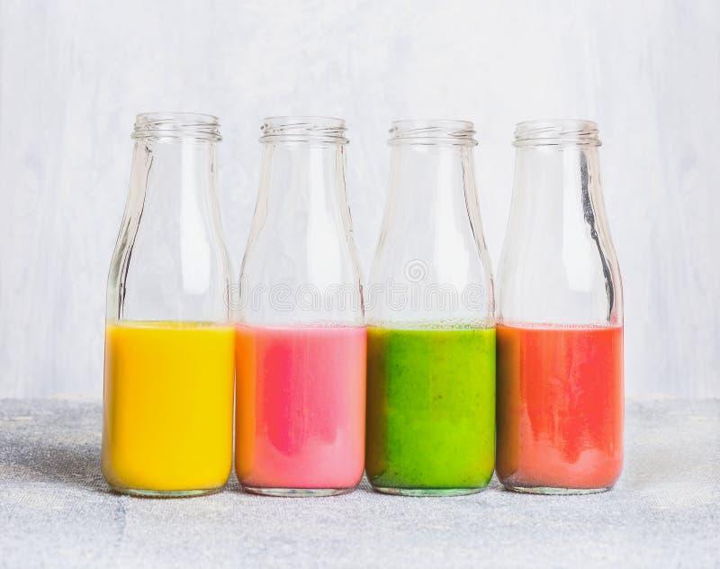 Assortimento variopinto dei frullati in bottiglie di vetro sulla tavola leggera, vista laterale fotografia stock