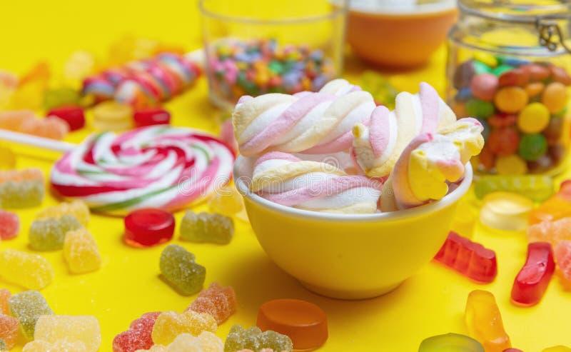 Assortimento variopinto delle caramelle sul fondo giallo di colore, vista del primo piano fotografia stock libera da diritti