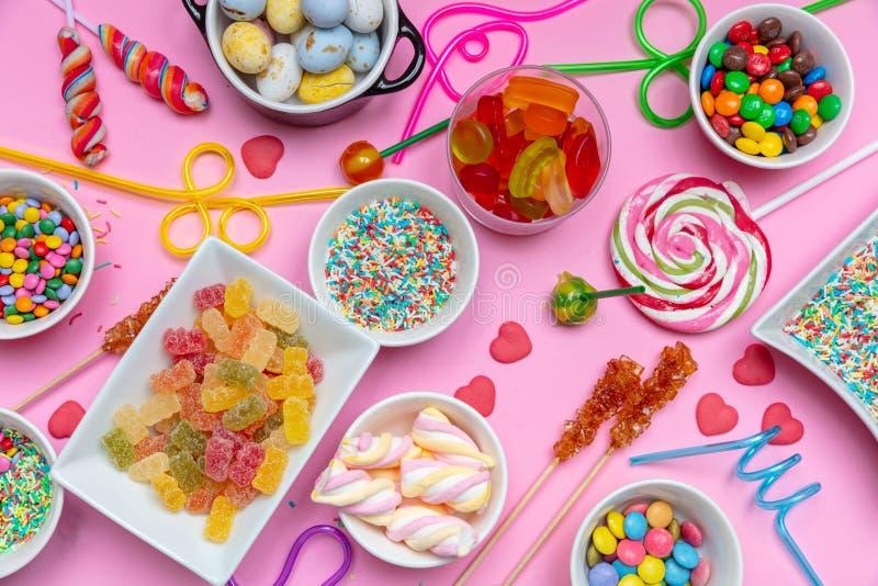 Assortimento variopinto delle caramelle sul fondo rosa di colore, vista superiore immagine stock