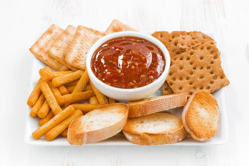 Assortimentsbroden, crackers en zoete, zure tomatensaus royalty-vrije stock afbeelding