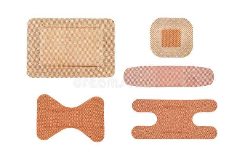 Assortment of adhesive bandages. An assortment sterile of adhesive bandages isolated on white stock image