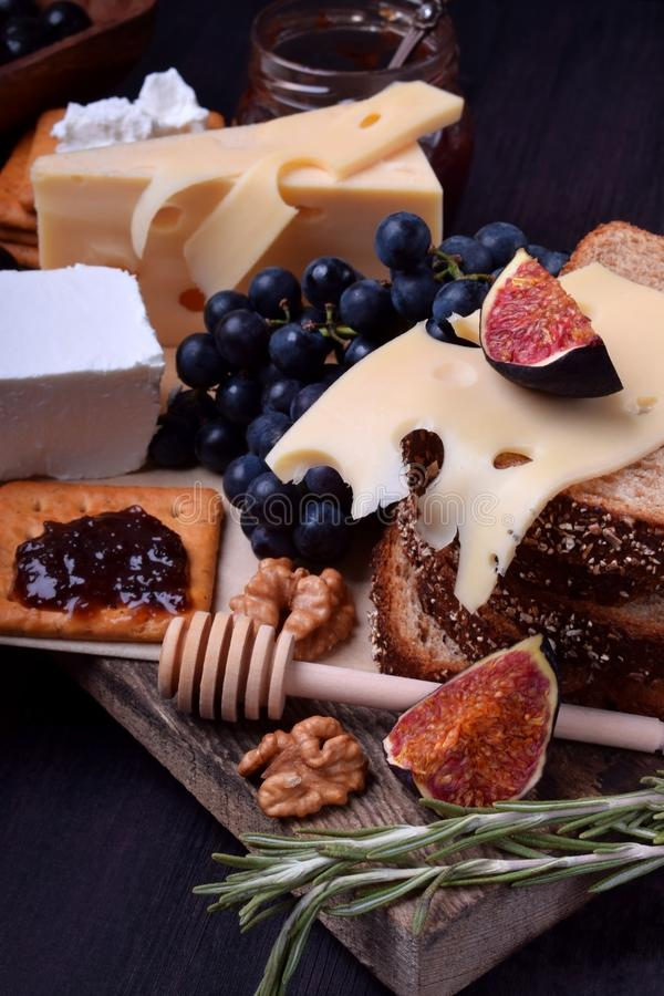 Assortment of appetizers: different sorts of cheese, crackers, grapes, nuts, olive marmalade, figs and olives royalty free stock image