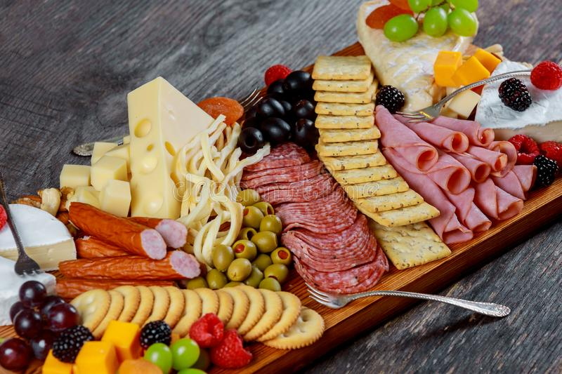 Assortment of appetizers: different sorts of cheese, crackers, grapes, nuts, olives against the wood background royalty free stock photos