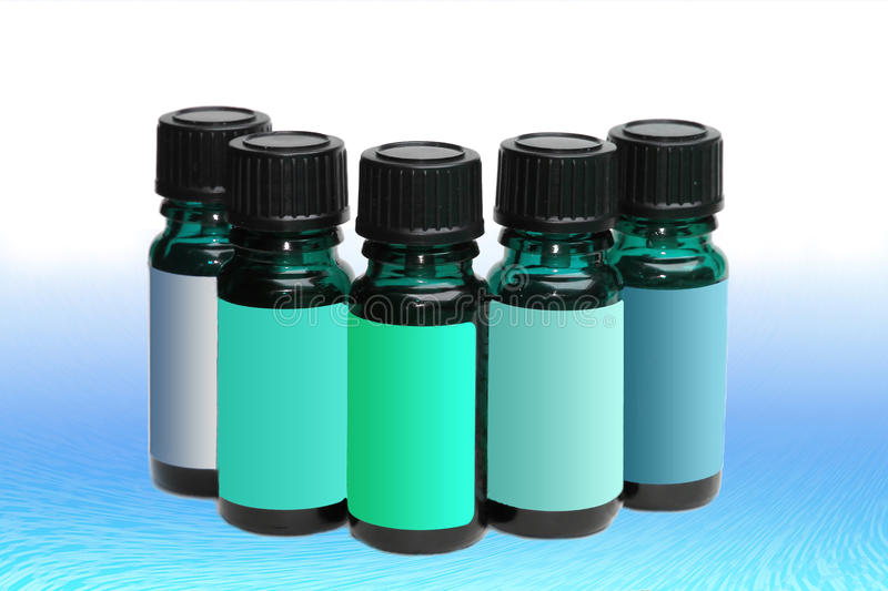 Assortment of aromatherapy bottles with blank labels in shades. Of blue royalty free stock photography