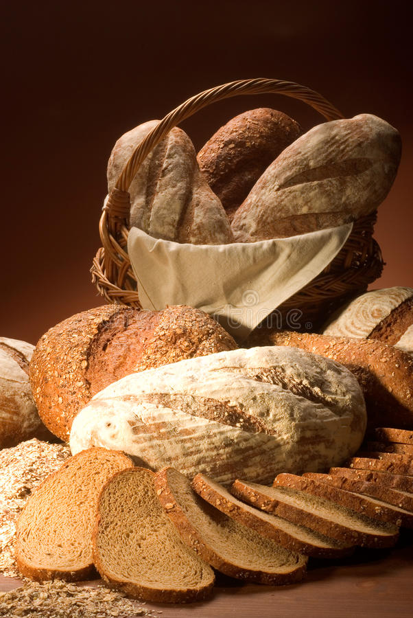 Assortment of baked bread over brown background royalty free stock images