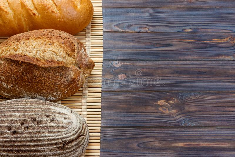 Assortment of baked bread on wood table. top view with copy space.  royalty free stock image