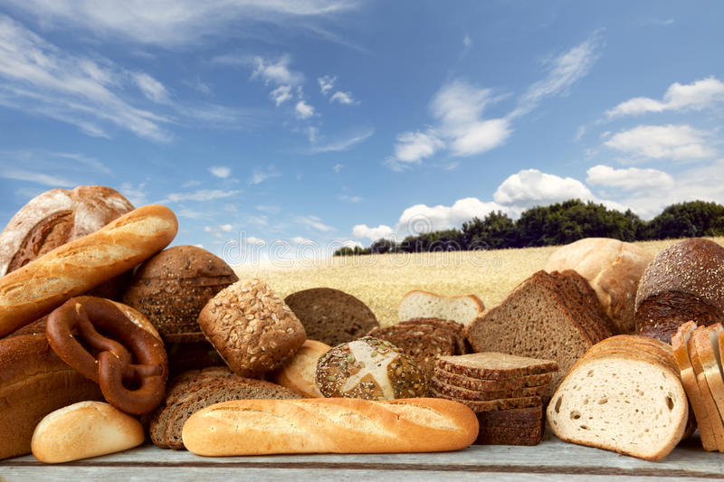 Assortment of baked goods. On Field of wheat under the blue sky background, Window Display stock photos