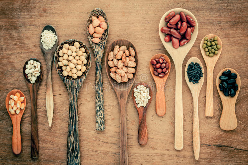 Assortment of beans and lentils in wooden spoon on teak wood background. mung bean, groundnut, soybean, red kidney bean , black b. Ean ,sesame, corn ,red bean stock photos