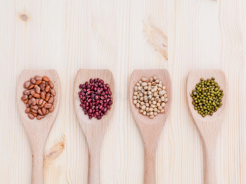 Assortment of beans and lentils in wooden spoon on wooden background. soybean, mung bean , red bean and brown pinto beans . stock photography