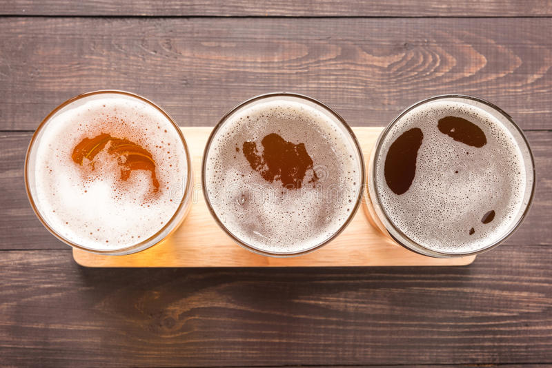 Assortment of beer glasses on a wooden background. Top view royalty free stock images