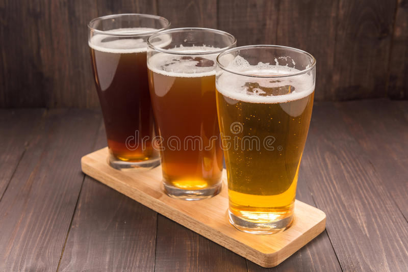 Assortment of beer glasses on a wooden table stock photo