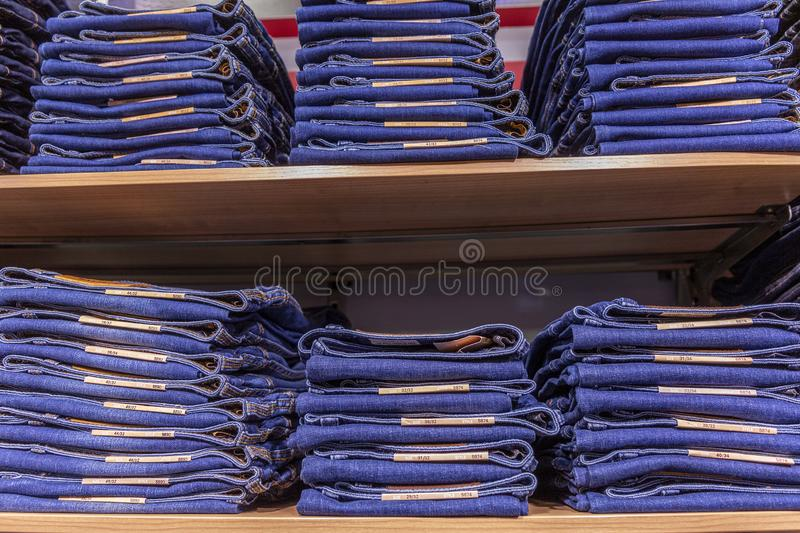 An assortment of blue jeans stacked on a shelf in a store. Close-up. Horizontal stock photography