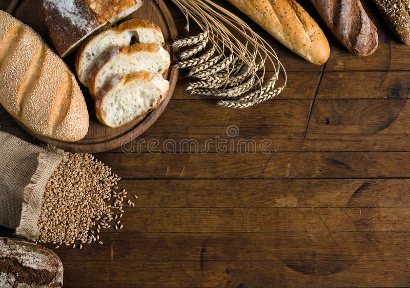 Assortment of bread and wheat on wooden table royalty free stock photo