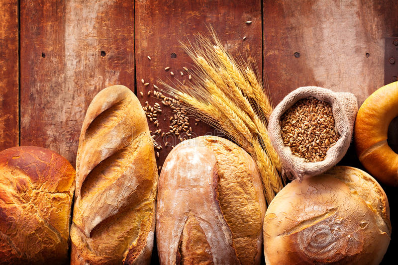 Assortment of bread on wooden table. Different type of bread on wooden background stock images