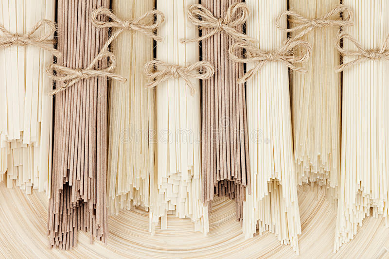 Assortment bundles of uncooked asian noodles close up on white wooden board background, top view. royalty free stock photo