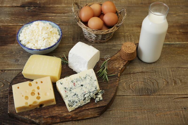 Assortment of cheese and cottage cheese and bottle of milk and chicken eggs. Organic farm dairy products and eggs. Assortment or various types of cheese stock photo