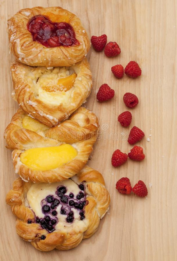 Assortment of cheese danishes puff pastry with blackberries, vanilla custard, cherry jam and fresh raspberries on wooden backgroun stock images