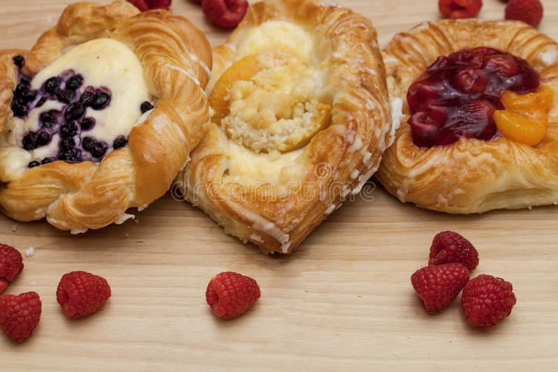 Assortment of cheese danishes puff pastry with blackberries, vanilla custard, cherry jam and fresh raspberries on wooden backgroun stock photos