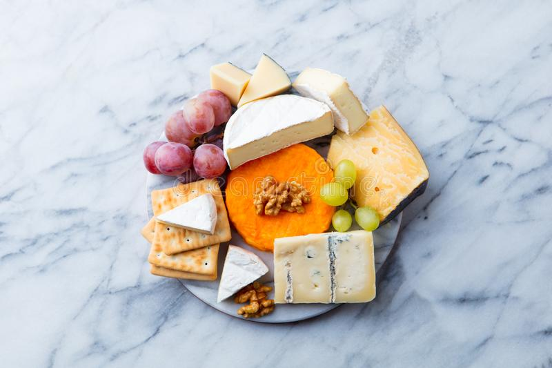 Assortment of cheese, grapes and crackers. Marble background. Top view. Copy space. stock photography