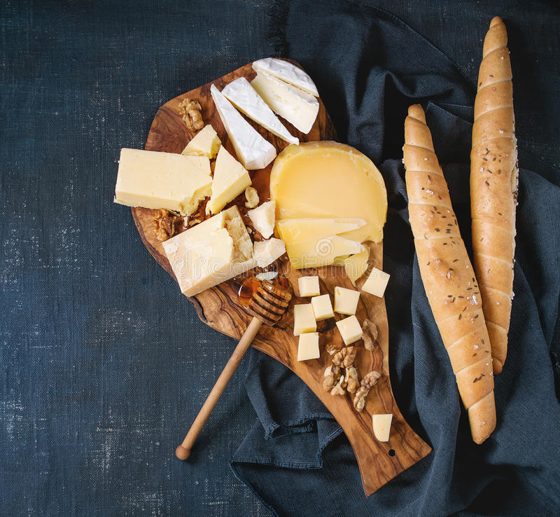 Assortment of cheese on wooden board. Cheese plate. Assortment of cheese with walnuts, honey and bread on olive wood serving board with textile over dark blue stock photography