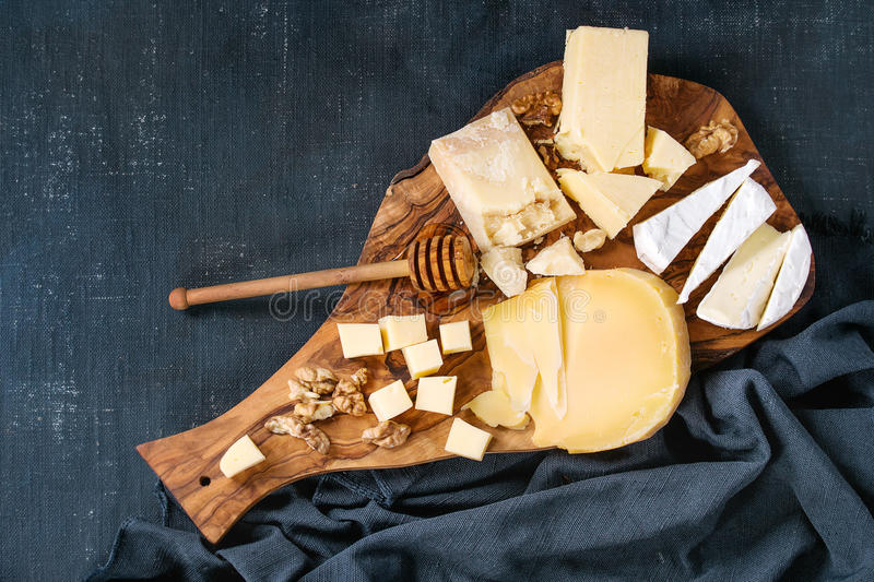 Assortment of cheese on wooden board. Cheese plate. Assortment of cheese with walnuts, honey from honey dipper on olive wood serving board with textile over dark stock image