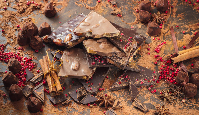 Assortment of chocolate bars, truffles, spices and cocoa powder. On dark background stock photography