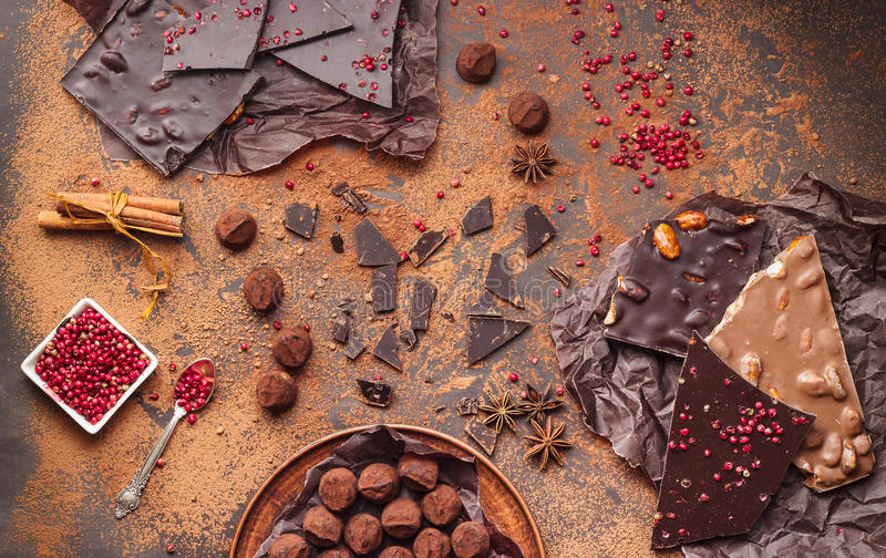 Assortment of chocolate bars, truffles, spices and cocoa powder. On dark background. Space for text, top view stock images
