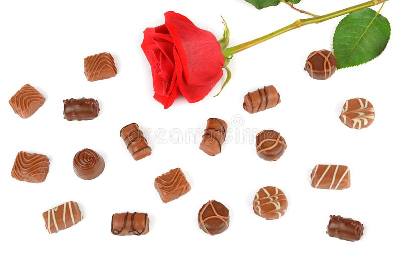 Assortment of chocolates and red rose isolated on white background. Flat lay, top view. royalty free stock image