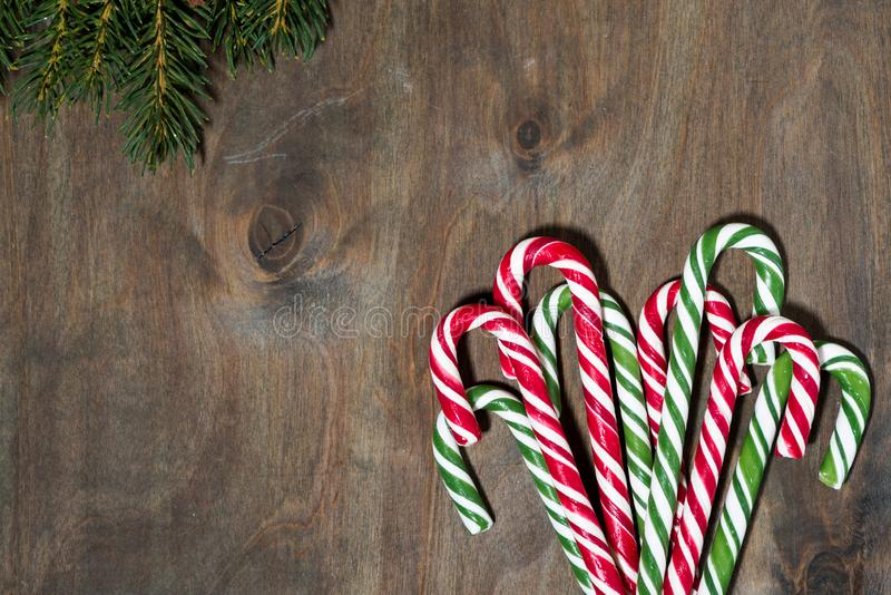 Assortment of christmas sugar candies and fir branches on grey background, top view closeup. Assortment of christmas sugar candies and fir branches on grey royalty free stock images