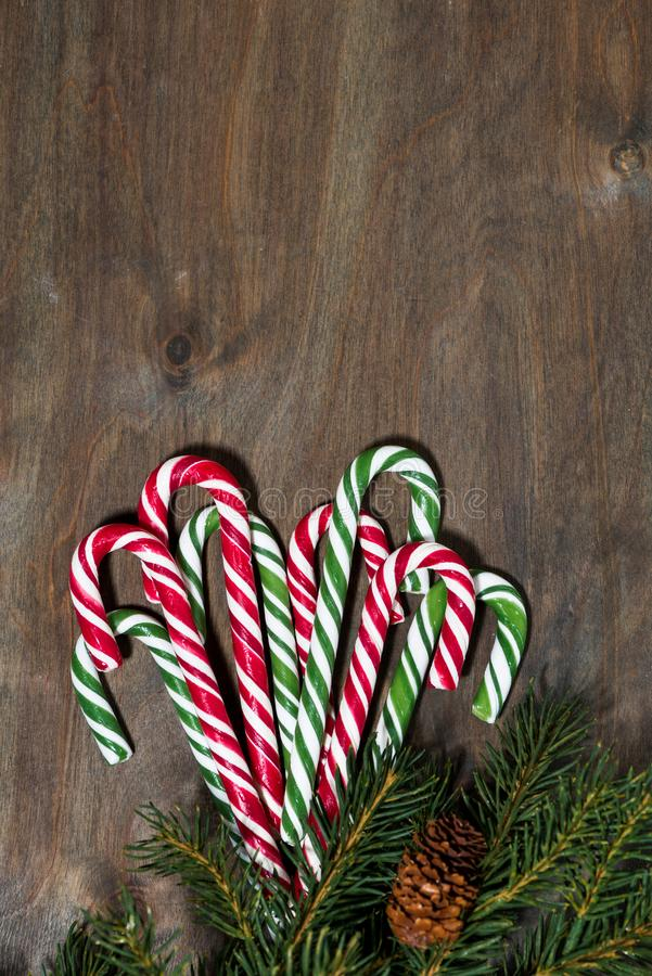 Assortment of christmas sugar candies and fir branches on grey wooden background, vertical closeup. Assortment of christmas sugar candies and fir branches on royalty free stock photography