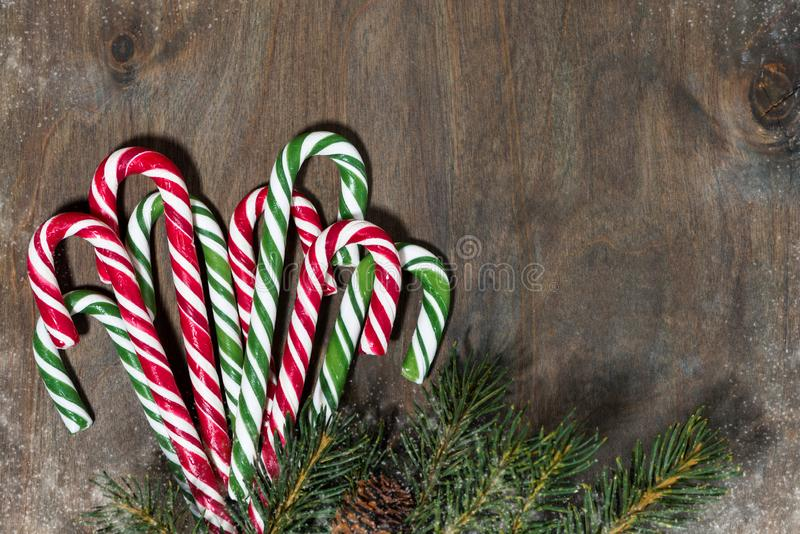 Assortment of christmas sugar candies and fir branches on grey wooden background, closeup. Top view royalty free stock images
