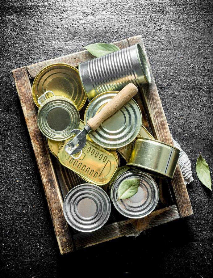 Assortment of closed tin cans with canned food on the tray. On black rustic background stock photography