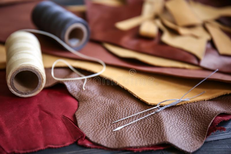 Assortment of colorful leather pieces with threads and needles on table stock image