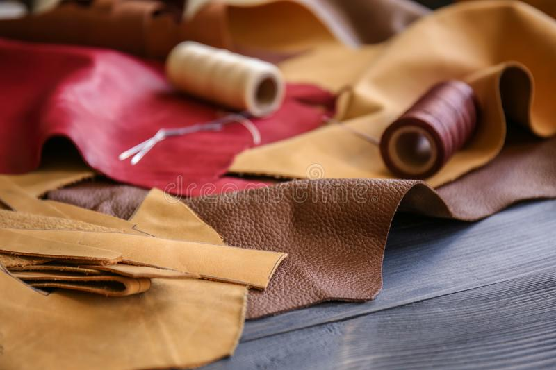 Assortment of colorful leather pieces with threads on table royalty free stock photos