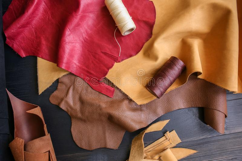 Assortment of colorful leather pieces with threads on table royalty free stock images