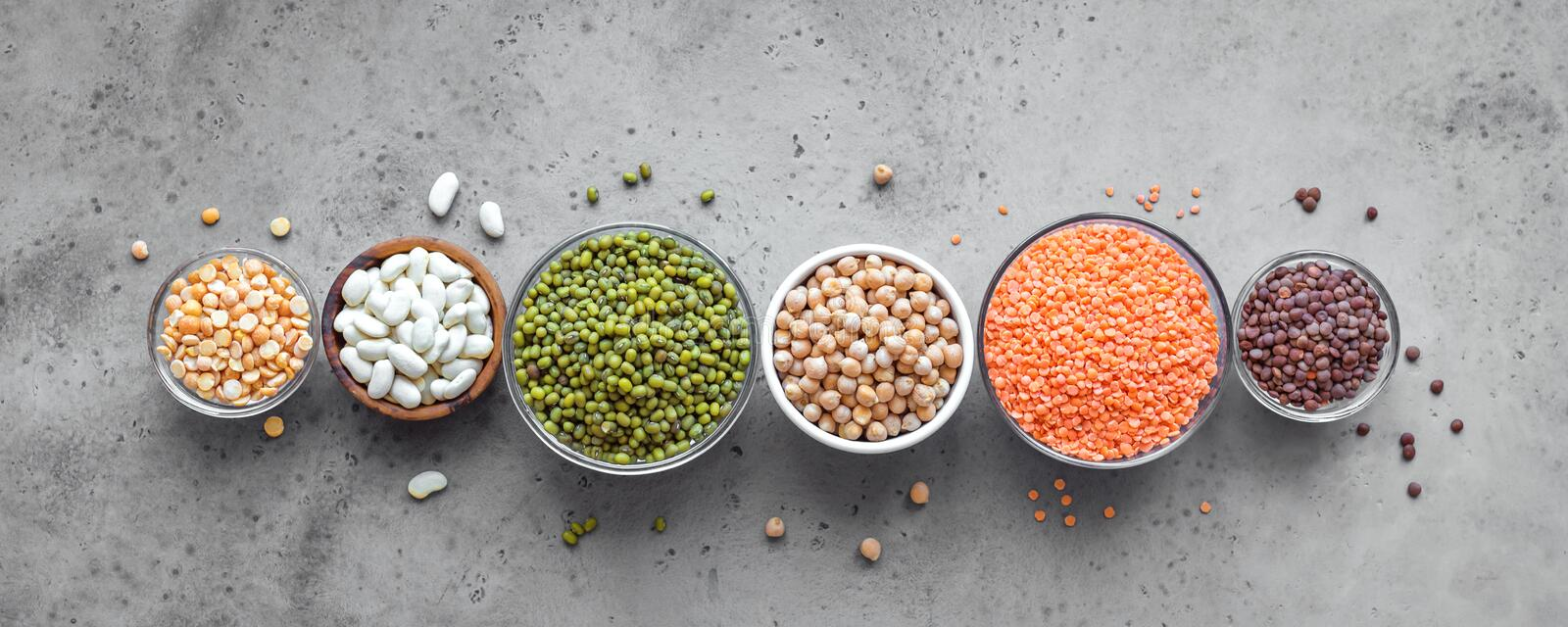 Legumes Assortment. Assortment of colorful legumes in bowls, lentils, kidney beans, chickpeas, mung, peas on concrete background, top view, banner. Healthy food stock photography