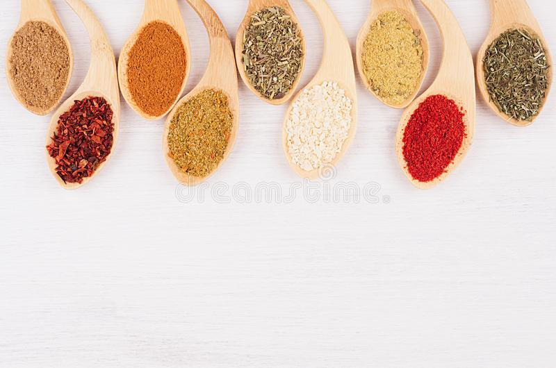 Assortment colorful powdered spices in bamboo spoons as decorative border. White wood background, top view, copy space royalty free stock photo