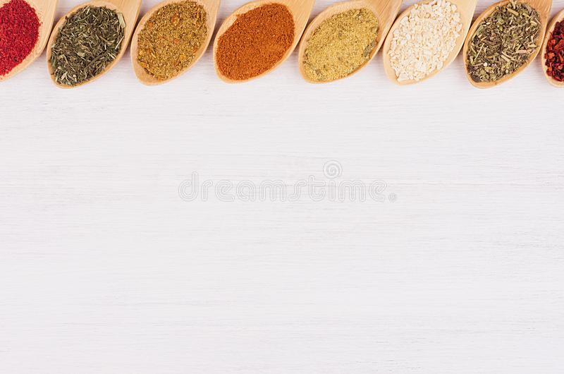 Assortment colorful powdered spices in bamboo spoons as decorative border. White wood background, top view, copy space stock image