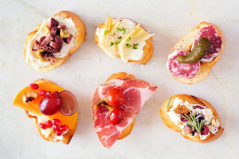 Assortment of crostini appetizers with a variety of toppings, top view over white marble stock image