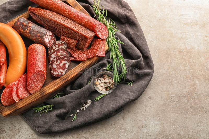 Assortment of delicious sausages on wooden board royalty free stock images