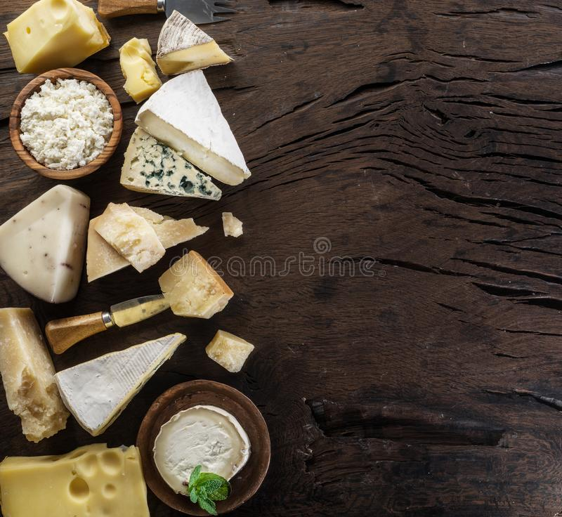 Assortment of different cheese types on old wooden background. Top view.  royalty free stock image